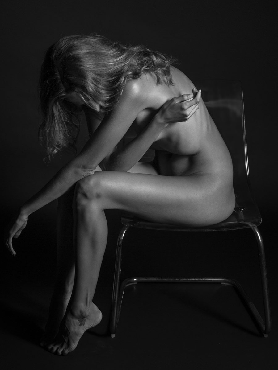 black and white photo of nude woman sitting in a chair